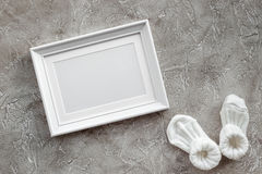 Theme for baby shower with shoes and white frame gray background top view space for text Royalty Free Stock Image