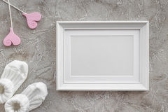 Theme for baby shower with shoes and white frame gray background top view space for text Royalty Free Stock Photos