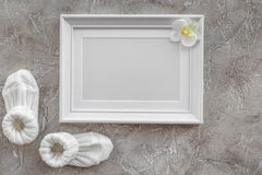 Theme for baby shower with shoes and white frame gray background top view space for text Royalty Free Stock Photography