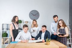 Theme is business and teamwork. A group of young Caucasian people office workers holding a meeting, briefing, working with papers stock photography