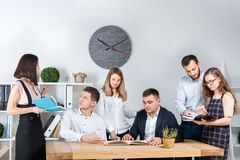 Theme is business and teamwork. A group of young Caucasian people office workers holding a meeting, briefing, working with papers stock image