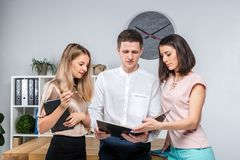 Theme business, teamwork and partnerships. A group of young people, three people, stand in an office near the table in royalty free stock photo