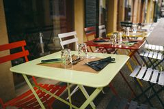 Theme cafes and restaurants. Exterior summer terrace of bright colors of street cafe shop in Europe in France. Preserved tables Wi royalty free stock photography