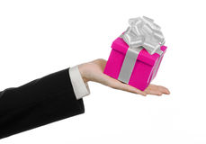 The theme of celebrations and gifts: hand holding a gift wrapped in pink box with white ribbon and bow, the most beautiful gift is Royalty Free Stock Images