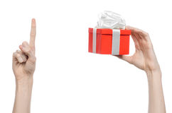 The theme of celebrations and gifts: hand holding a gift wrapped in red box with white ribbon and bow, the most beautiful gift iso Royalty Free Stock Photography