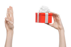 The theme of celebrations and gifts: hand holding a gift wrapped in red box with white ribbon and bow, the most beautiful gift iso Stock Images