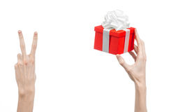 The theme of celebrations and gifts: hand holding a gift wrapped in red box with white ribbon and bow, the most beautiful gift iso Stock Image