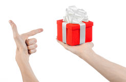 The theme of celebrations and gifts: hand holding a gift wrapped in red box with white ribbon and bow, the most beautiful gift iso Stock Photos