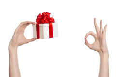 The theme of celebrations and gifts: hand holding a gift wrapped in white box with red ribbon and bow, the most beautiful gift iso Royalty Free Stock Image