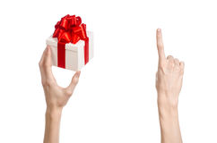 The theme of celebrations and gifts: hand holding a gift wrapped in white box with red ribbon and bow, the most beautiful gift iso Stock Image
