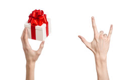 The theme of celebrations and gifts: hand holding a gift wrapped in white box with red ribbon and bow, the most beautiful gift iso Royalty Free Stock Photography