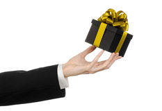 The theme of celebrations and gifts: a man in a black suit holding a exclusive gift packaged in a black box with gold ribbon and b Stock Photo