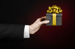The theme of celebrations and gifts: a man in a black suit holding a exclusive gift packaged in a black box with gold ribbon, beau Stock Image