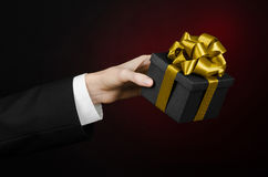 The theme of celebrations and gifts: a man in a black suit holding a exclusive gift packaged in a black box with gold ribbon, beau Royalty Free Stock Photos