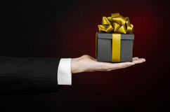 The theme of celebrations and gifts: a man in a black suit holding a exclusive gift packaged in a black box with gold ribbon, beau Royalty Free Stock Image