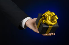 The theme of celebrations and gifts: a man in a black suit holding a exclusive gift packaged in a black box with gold ribbon, beau Royalty Free Stock Photography