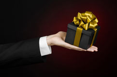 The theme of celebrations and gifts: a man in a black suit holding a exclusive gift packaged in a black box with gold ribbon, beau Royalty Free Stock Images