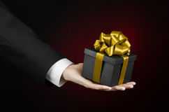 The theme of celebrations and gifts: a man in a black suit holding a exclusive gift packaged in a black box with gold ribbon, beau Stock Photos