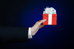 The theme of celebrations and gifts: a man in a black suit holding a exclusive gift wrapped in red box with white ribbon, beautifu Stock Photos