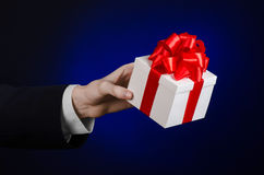 The theme of celebrations and gifts: a man in a black suit holding a exclusive gift wrapped in white box with red ribbon, beautifu Stock Photos