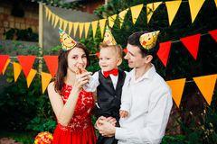Theme children birthday party. Family father and mother holding son of one year on the background of greenery and festive decor, g. Arlands and colored ornaments stock image
