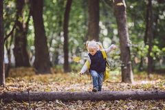 The theme children outdoor activities. Funny little baby Caucasian blond girl walks through forest overcoming obstacles, tree fell stock images