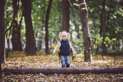 The theme children outdoor activities. Funny little baby Caucasian blond girl walks through forest overcoming obstacles, tree fell royalty free stock photos