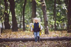 The theme children outdoor activities. Funny little baby Caucasian blond girl walks through forest overcoming obstacles, tree fell royalty free stock image