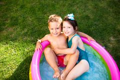 Theme is a children`s summer vacation. Two Caucasian children, brother and sister, sit in a perched round pool with water in the stock photos