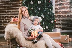 Theme Christmas holidays winter new year. A young stylish Caucasian mother holds her son in her arms for 1 year in a funny shirt royalty free stock photos