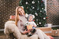 Theme Christmas holidays winter new year. A young stylish Caucasian mother holds her son in her arms for 1 year in a funny shirt stock image
