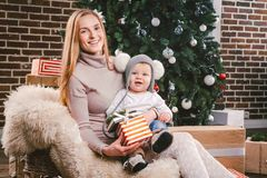 Theme Christmas holidays winter new year. A young stylish Caucasian mother holds her son in her arms for 1 year in a funny shirt royalty free stock image