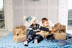 Theme Christmas morning. Two child Caucasian boy and girl brother and sister are sitting on the bed in an embrace with a smile and stock photos