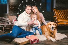 Theme Christmas and New Year family circle and domestic pet. Mom dad and child 1 year old Caucasian woman sitting on stock images