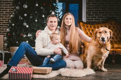 Theme Christmas and New Year family circle and domestic pet. Mom dad and child 1 year old Caucasian woman sitting on stock photo