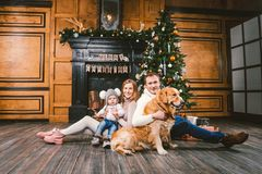 Theme Christmas and New Year family circle. Young Caucasian family with 1 year old child dog breed Labrador Golden Retriever. Sitting on wooden floor home in stock photos