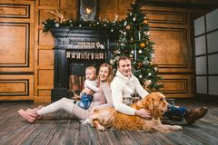 Theme Christmas and New Year family circle. Young Caucasian family with 1 year old child dog breed Labrador Golden Retriever. Sitting on wooden floor home in royalty free stock images
