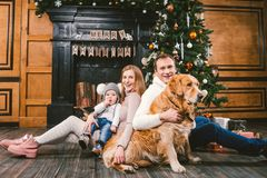 Theme Christmas and New Year family circle. Young Caucasian family with 1 year old child dog breed Labrador Golden Retriever. Sitting on wooden floor home in stock photo