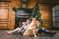 Theme Christmas and New Year family circle. Young Caucasian family with 1 year old child dog breed Labrador Golden Retriever. Sitting on wooden floor home in royalty free stock photos