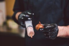 Theme cooking. Hands close up. young Caucasian man in black uniform and latex gloves in kitchen. restaurant prepares ground beef royalty free stock image