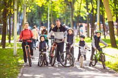 Theme family active sports outdoor recreation. A group of people is a big family of 6 people standing posing on mountain. Bikes in a city park on a road on a royalty free stock photos