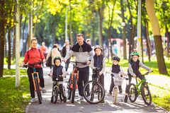 Theme family active sports outdoor recreation. A group of people is a big family of 6 people standing posing on mountain. Bikes in a city park on a road on a royalty free stock image