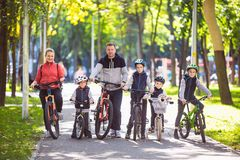 Theme family active sports outdoor recreation. A group of people is a big family of 6 people standing posing on mountain. Bikes in a city park on a road on a royalty free stock photography