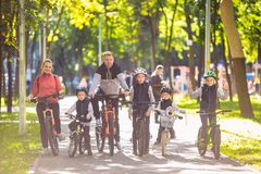 Theme family active sports outdoor recreation. A group of people is a big family of 6 people standing posing on mountain. Bikes in a city park on a road on a royalty free stock photo