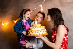 Theme family holiday childrens birthday and blowing out candles on large cake. young family of three people standing and holding 5 royalty free stock photo