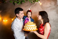 Theme family holiday childrens birthday and blowing out candles on large cake. young family of three people standing and holding 5. Year old daughter in yard Royalty Free Stock Images