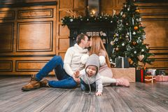 Family holiday New Year and Christmas. Young caucasian family mom dad son 1 year sit wooden floor near fireplace christmas tree on stock photos