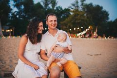 Theme of family summer vacations on the beach. Caucasian man and woman dad and mom hug a small baby son sitting on his hands. stock images