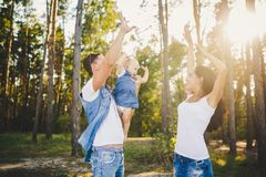 Theme family vacation in the forest. A small child has daughter with daddy on shoulders, mother stands next to her raised arms and Stock Photography