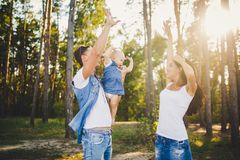 Theme family vacation in the forest. A small child has daughter with daddy on shoulders, mother stands next to her raised arms and Stock Images